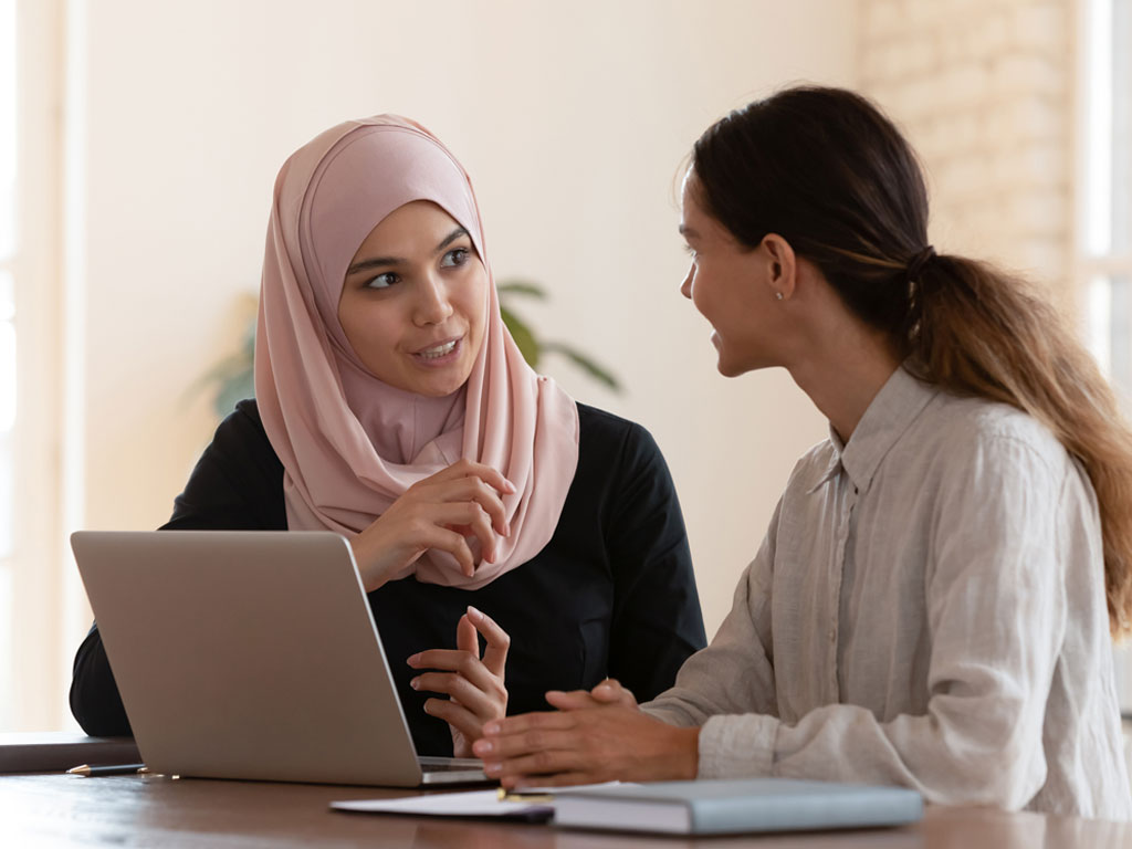 Two colleagues talking near a computer.