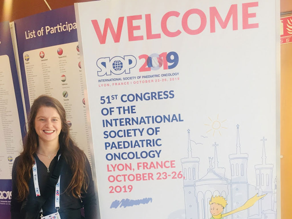 Sierra standing next to a poster during the 51st Congress of the International Society of Pediatric Oncology in Lyon France