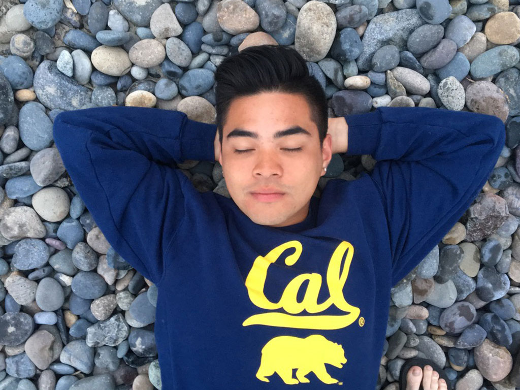 Ramil relaxing with his eyes closed on a bed of rocks