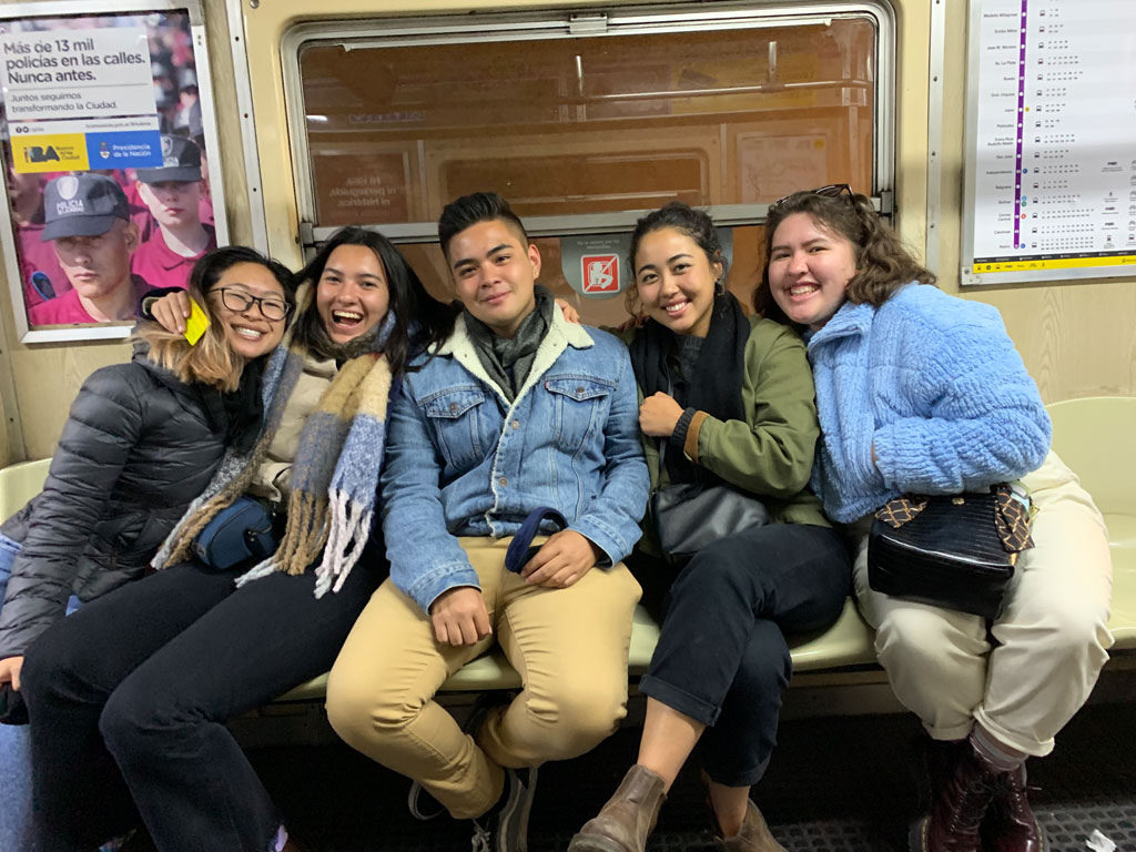 Ramil and friends smiling for the camera while on public transportation