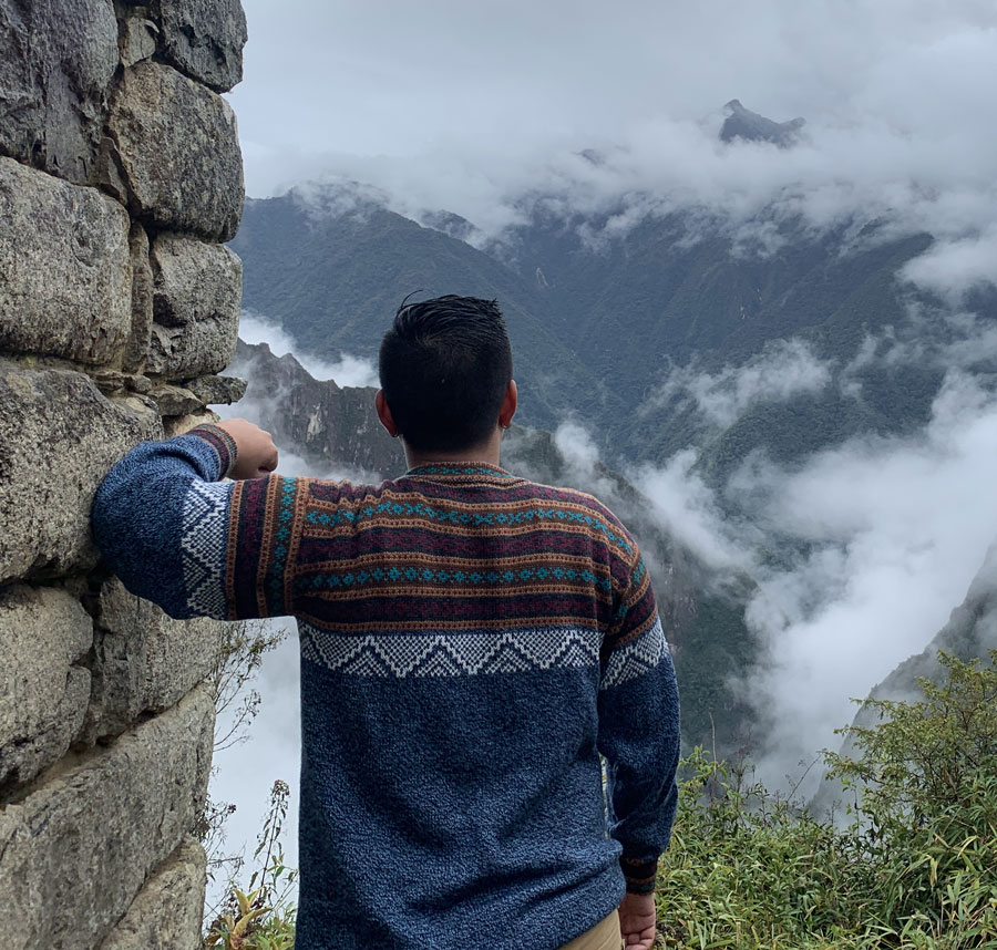Ramil leaning against a stone wall looking out into nature.